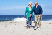 Senior Couple Walking Along Beach Together — Stock Photo