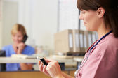 Nurse Using Mobile Phone At Nurses Station — Stock Photo