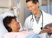 Doctor usando tableta digital hablando con paciente senior — Foto de Stock