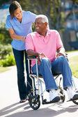 Carer Pushing Senior Man In Wheelchair — Stock Photo