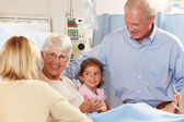 Family Visiting Senior Female Patient In Hospital Bed — Stock Photo