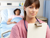 Portrait Of Nurse With Patient In Background — Stock Photo