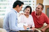Finansiell rådgivare talar till äldre par hemma — Stockfoto