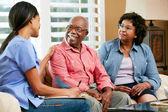 Sjuksköterska att göra anteckningar under hem besök med äldre par — Stockfoto