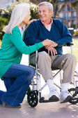 Senior Woman Pushing Husband In Wheelchair — Stock Photo