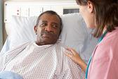 Infermiera parlando con paziente maschio anziano su ward — Foto Stock