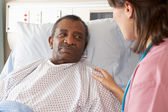 Nurse Talking To Senior Male Patient On Ward — Foto Stock