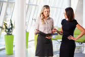 Two Businesswomen Having Informal Meeting In Modern Office — Stock Photo