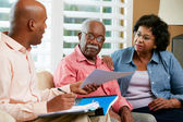 Financial Advisor Talking To Senior Couple At Home — Stok fotoğraf