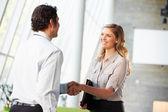 Empresário e empresária apertando as mãos no escritório — Foto Stock