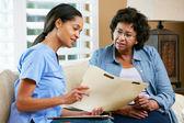 Enfermeira registros a discutir com a paciente do sexo feminino sênior durante o repouso — Foto Stock
