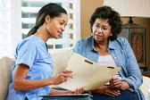 Nurse Discussing Records With Senior Female Patient During Home — Stockfoto