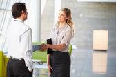 Zakenman en zakenvrouw schudden handen in office — Stockfoto
