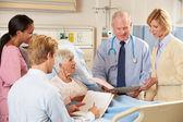 Lékařský tým hostující starší pacientka v posteli — Stock fotografie