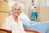 Portrait Of Senior Female Patient Seated In Chair By Hospital Be — Stock Photo