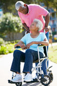 Senior Woman Pushing Unhappy Husband In Wheelchair — Stock Photo