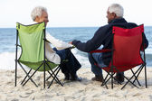 Senior Couple Sitting On Beach In Deckchairs — Stock Photo