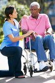 Carer Pushing Unhappy Senior Man In Wheelchair — Stock Photo