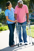 Carer Helping Senior Man With Walking Frame — Foto Stock