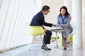 Zakenman en zakenvrouw voldoen aan in moderne kantoor — Stockfoto