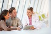 Dottore femminile utilizzando la tavoletta digitale, parlando con i pazienti — Foto Stock