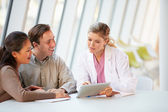 Female Doctor Using Digital Tablet Talking With Patients — Stockfoto