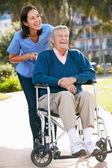 Opiekun pchanie starszy człowiek na wózku inwalidzkim — Zdjęcie stockowe