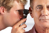 Doctor Examining Male Patient's Ears — Stockfoto