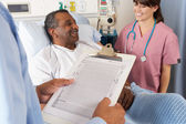 Doctor Looking At Chart With Senior Male Patient — Stockfoto