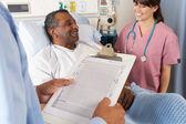 Arts kijken grafiek met senior mannelijke patiënt — Stockfoto