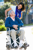 Adult Daughter Pushing Senior Father In Wheelchair — Stock Photo