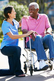 Carer Pushing Senior Man In Wheelchair — Stock Photo
