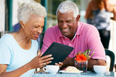 Senior Couple Using Tablet Computer At Outdoor Cafe — Foto Stock