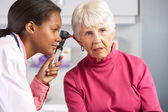 Doctor Examining Senior Female Patient's Ears — Stockfoto