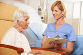 Nurse Taking Notes From Senior Female Patient Seated In Chair By — Stock Photo