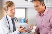 Docteur discutant des dossiers avec le patient à l'aide de tablette numérique — Photo