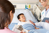 Doctor Using Digital Notepad Whilst Visiting Child Patient — Stock Photo