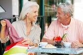 Senior pareja disfrutando de refrigerio en el café al aire libre después de ir de compras — Foto de Stock