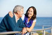 Senior man met volwassen dochter kijkt uit over de reling op zee — Stockfoto
