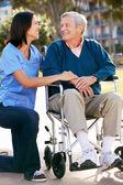 Badante, spingendo l'uomo anziano in sedia a rotelle — Foto Stock