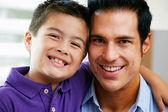 Portret van vader en zoon zittend op de bank thuis — Stockfoto