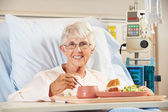 Senior Female Patient Eating Meal In Hospital Bed — Stock Photo