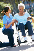 Carer Pushing Unhappy Senior Woman In Wheelchair — Stock Photo