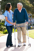 Carer Helping Senior Man With Walking Frame — Stok fotoğraf