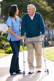 Cuidador, ajudando o homem sênior com moldura para caminhadas — Foto Stock