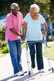Senior Man Helping Wife With Walking Frame — Stock Photo