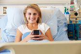 Teenage Female Patient Using Mobile Phone In Hospital Bed — Stock Photo