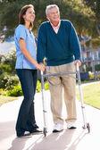 Carer Helping Senior Man With Walking Frame — Stock Photo