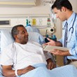 Doctor Visiting Senior Male Patient On Ward — Stock Photo #24650021