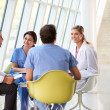 Foto Stock: Medical Team Meeting Around Table In Modern Hospital